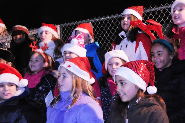 "Grafenwoehr Elementary School students sing a version of ""Frosty the Snowman"" that jumped from sweet and traditional to rock and roll during the Christmas tree lighting ceremony in Grafenwoehr, Dec. 4."