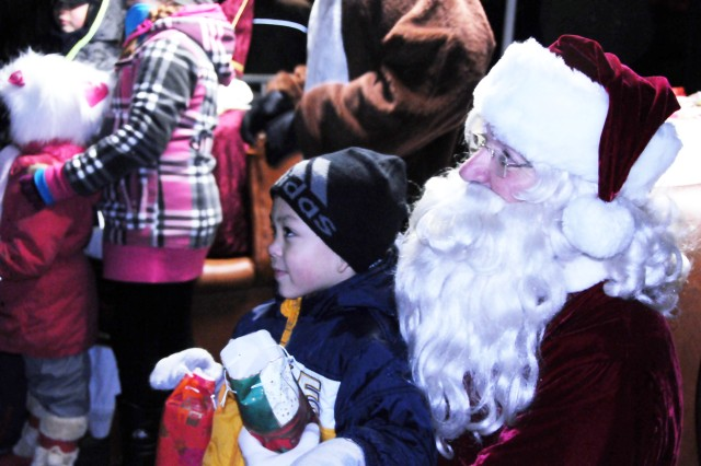 Joshua Parker, 6, poses with Santa while his dad takes his picture during the Tree Lighting Ceremony in Grafenweohr, Dec. 4.