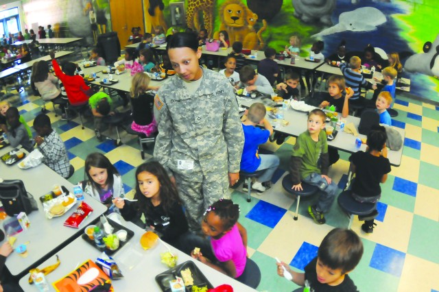 Fort Lee volunteer Pfc. Kristal Doyle talks with children at Ecoff Elementary School in Chester during a stint as a cafeteria monitor Nov. 28. Doyle said she believes in community service and wants the community to see Soldiers in a positive light.