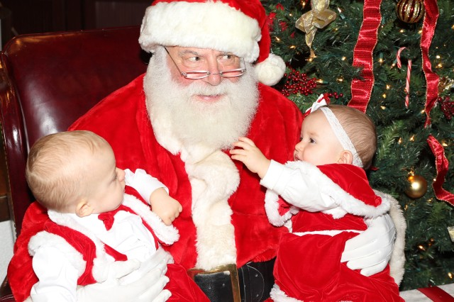 A pair of one-year-old twins sit on Santa's lap during the annual Holiday Magic event in Heidelberg, Germany, Nov.27.