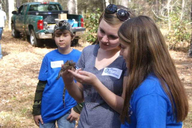 Megan and Alexis Matthews, military Family members, hold a baby alligator at the Southeast Regional Outdoor Sports Day at Mabson Community Education Forest in Ozark where they also participated in archery and air rifle shooting Nov. 11.