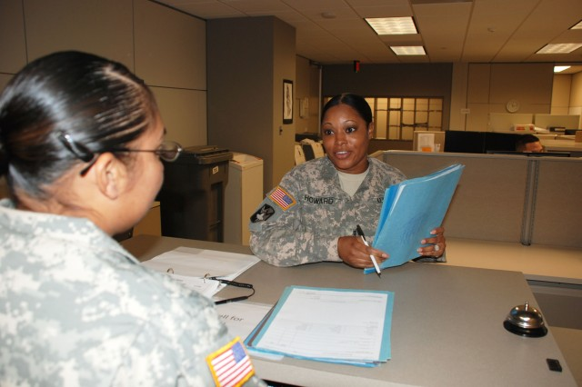 Chief Warrant Officer 3 Christina Howard assists a customer at the S1 (Personnel) office of the 470th Military Intelligence Brigade.