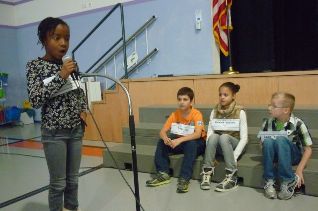 Fourth-grader Camille Johnson spells her way to victory during the Netzaberg Elementary School Spelling Bee while fellow contenders look on.