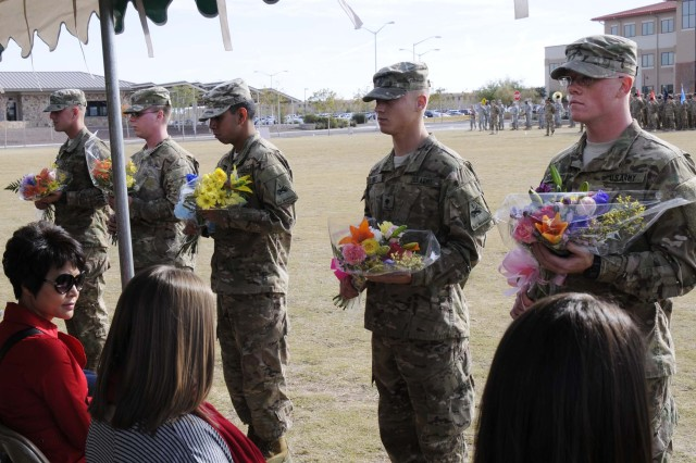 Soldiers present bouquets of flowers to spouses of deploying soldiers during the casing ceremony for 1st Brigade Combat Team, 1st Armored Division, at Fort Bliss, Texas, Dec. 4.  The ceremony was held to signify the brigade's upcoming deployment to Afghanistan.