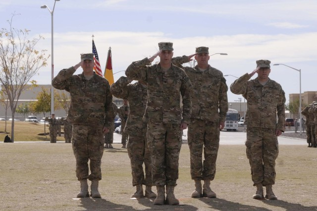 Soldiers salute in formation during the casing ceremony for 1st Brigade Combat Team, 1st Armored Division, at Fort Bliss, Texas, Dec. 4.  The ceremony was held to signify the brigade's upcoming deployment to Afghanistan.