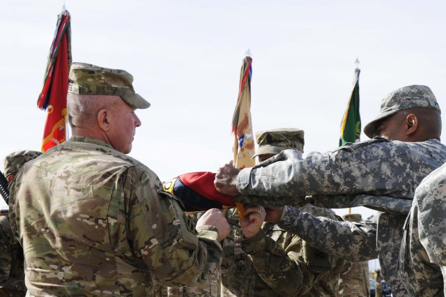 Maj. Gen. Dana J.H. Pittard, 1st Armored Division and Fort Bliss commanding general, assists Col. Ken Adgie, 1st Brigade Combat Team, 1st Armored Division brigade commander, case the brigade colors duirng a ceremony at Fort Bliss, Texas, Dec. 4.  The ceremony was held to signify the brigade's upcoming deployment to Afghanistan.