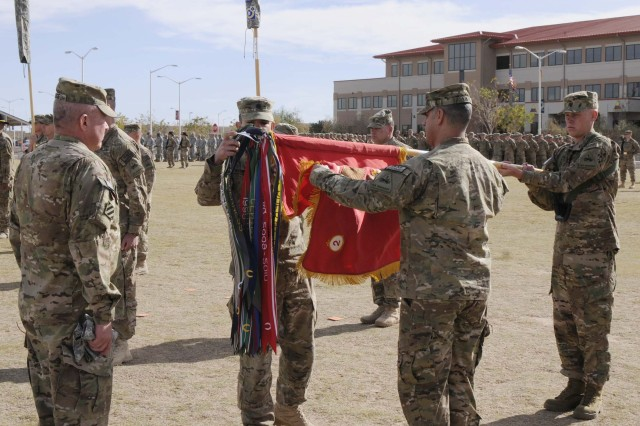 Col. Ken Adgie, 1st Brigade Combat Team, 1st Armored Division brigade commander, helps Lt. Col. Paul C. Weyrauch, 2nd Battalion, 3rd Field Artillery (Gunners) battalion commander, and Command Sgt. Maj. Orlando Ramos, battalion command sergeant major, case the battalion colors during a ceremony at Fort Bliss, Texas, Dec. 4.  The ceremony was held to signify the brigade's upcoming deployment to Afghanistan.