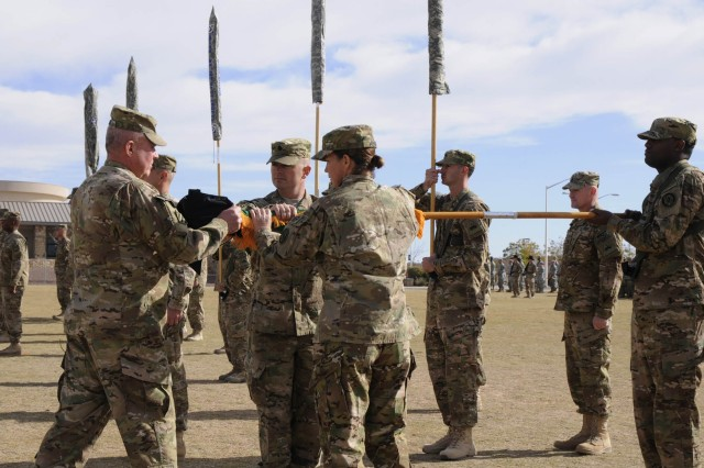 Col. Ken Adgie, 1st Brigade Combat Team, 1st Armored Division brigade commander, assists the command team from 115th Military Police Battalion case their battalion colors during a ceremony at Fort Bliss, Texas, Dec. 4.  The ceremony was held to signify the brigade's upcoming deployment to Afghanistan.