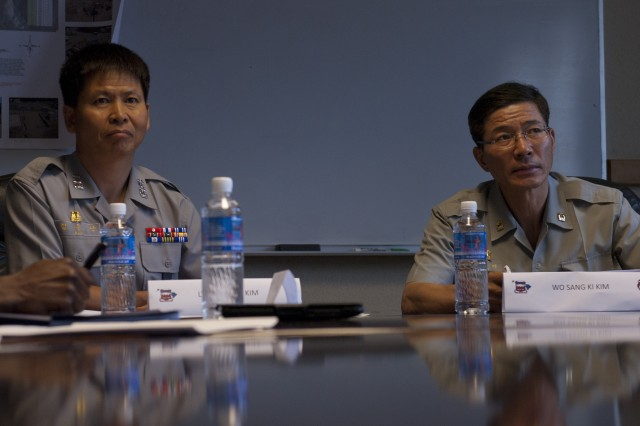 (left to right) Lt. Col. Lt. Col. Ju-Nan Kim, the Republic of Korean officer in charge of their Combined Terrain Analysis Team, and his senior warrant officer, Warrant Officer Sang-Ki Kim, listen to a brief at the 70th Geospatial Engineer Company, 65th Engineer Battalion, 130th Engineer Brigade, 8th Theater Sustainment Command, during a subject matter expert exchange between the ROK and the U.S. Army, Nov. 4-9.