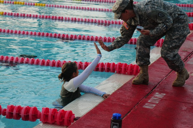 Staff Sgt. Stephanie White, a technical engineer from THS, HHC 130th Eng. Bde., 8th TSC, is congratulated for completing the 200 meter swim during the GAFPB testing, November 5, at Richardson Pool, Schofield Barracks.