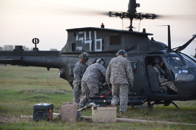 Soldiers from the Company E, 4th Battalion, 101st Aviation Regiment, pumps gas into an OH-58D Kiowa Warrior helicopter at a jump-forward arming and refueling point during a Joint Operations Aviation Exercise on Fort Bragg, N.C., Aug. 22. The jump-FARP will give pilots immediate access to their mission-essential supplies. (U.S. Army photo by Sgt. Shanika L. Futrell, 159th Combat Aviation Brigade Public Affairs/RELEASED)