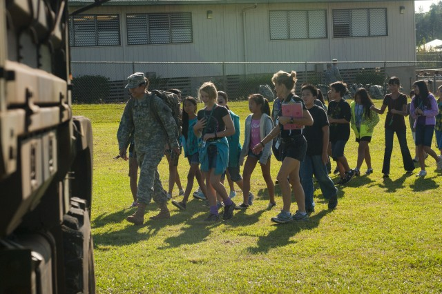 Soldiers with the 65th Engineer Battalion, 130th Engineer Brigade, 8th Theater Sustainment Command, walks with students from Mililani Middle School with a ruck sack full of student donated toys during a toy drive for Toys for Tots and the Make a Wish Foundation at the school, Nov. 30.