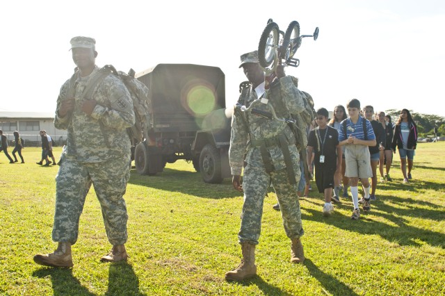 Soldiers with the 65th Engineer Battalion, 130th Engineer Brigade, 8th Theater Sustainment Command, carry student donated toys around the soccer field of the Mililani Middle School during a toy drive for Toys for Tots and the Make a Wish Foundation at the school, Nov. 30.