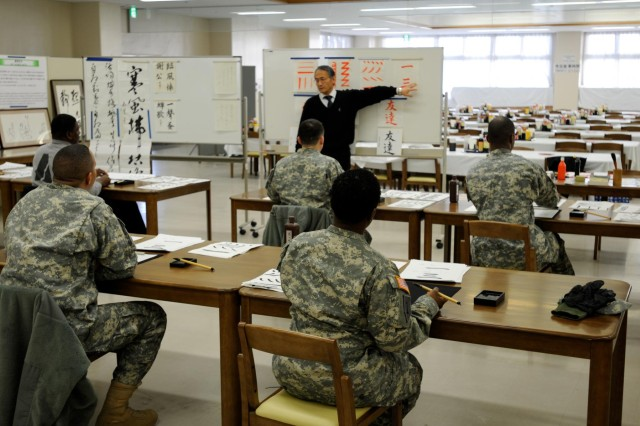 As part of a cultural exchange, soldiers at Camp Sendai, Japan, practice writing calligraphy.