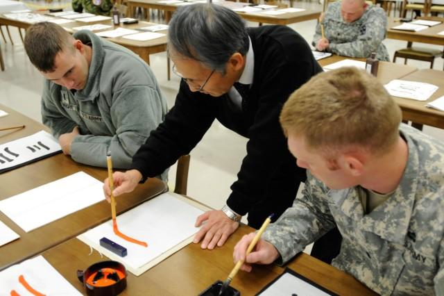 Hitoshi Tamiya demonstrates calligraphy to 1st Lt. J.C. Wright and 1st Lt. John Spies at a cultural exchange at Camp Sendai, Japan.