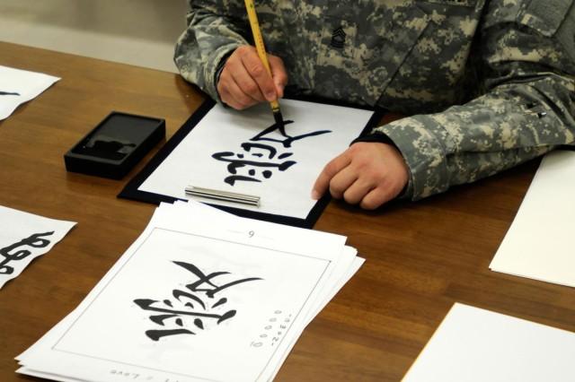Master Sgt. Jose Santiago practices calligraphy as part of a cultural exchange at Camp Sendai, Japan, during Yama Sakura 63.