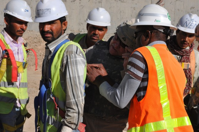 Jeff Ice, a safety and occupational health specialist who deployed to Kandahar from the U.S. Army Corps of Engineers New York District, checks the safety harness on a construction worker in Kandahar, Afghanistan. The highest frequency of fall-related fatalities is experienced by the construction industry. Safety and occupational health specialists visit construction sites daily to make sure safety regulations are complied with and to recommend measures that can reduce hazards.