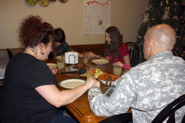 Chaplain (Capt.) Eric Miller, his wife, Stephanie, and their four children, Kathryn, Julian, Elizabeth and Abigail, pray over their evening meal in their home at Fort Bragg's satellite neighborhood, Linden Oakes, in Cameron, N.C., Dec 3.  Eric serves as the chaplain for the 122nd Aviation Sustainment Brigade, 82nd Combat Aviation Brigade.  The Miller family, originally from Allentown, Pa., is one of three 82nd CAB families who are finalists for the Fort Bragg Family of the Year for 2012.