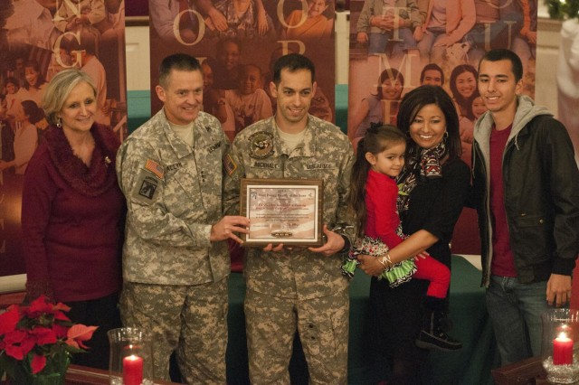 XVIII Airborne Corps Commander Lt. Gen. Daniel Allyn and his wife, Debbie, present a plaque to the Buckhalt family, of 2nd Aviation Assault Battalion, 82nd Combat Aviation Brigade, for their nomination for the 2012 Fort Bragg Family of the Year, Dec. 6. Capt. Allen Buckhalt, his wife, Maj. (Ret.) Bonnie Buckhalt, and their children, Joel, 18, and Ava, 4, were among three 82nd CAB families who were finalists for the family of the year. Allen, of Miami, is a UH-60 Blackhawk helicopter pilot who serves as the commander for Company B, 2nd Aviation Assault Battalion, 82nd CAB, and Bonnie as the company Family Readiness Group leader. (Photo by U.S. Army Staff Sgt. April Campbell, 82nd Combat Aviation Brigade Public Affairs)