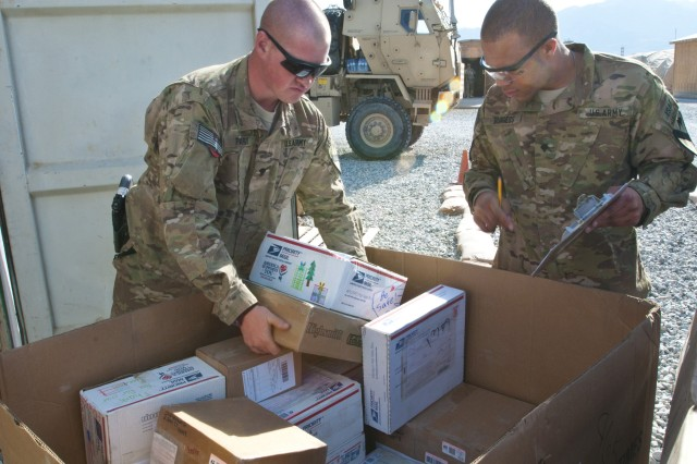 """Spc. Terrance Burgess, a human resources specialist and the primary mail clerk for Forward Operating Base Gamberi, Afghanistan, writes down the names of those who received mail while Spc. Zachariah Parvi, an air defense battle management system operator and the assistant mail clerk for the FOB, sorts through a postal """"kicker"""" boxes, which arrived at the base Dec. 9, 2012. Nearly 600 pieces of mail are processed through the FOB every week by Burgess, Parvi and several other members of the 4th Brigade Combat Team, 1st Cavalry Division, bringing much needed morale boosts to the """"Long Knife"""" Soldiers stationed there."""