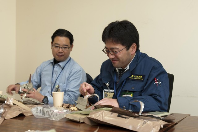 Yukinao Kitahara (left) of the South Kauto Defense Bureau and Mr. Iga of of the Tohoku Defense Bureau share their new experience eating a MRE (meal ready to eat) while conducting a visit to Camp Sendai to observe the Yama Sakura exercise.