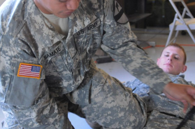 """FORT HOOD, Texas--Pvt. Travis Samate, from Colorado Springs, Colo. and a signal support systems specialist with HHT, 4th """"Dark Horse"""" Sqdn., 9th U.S. Cav. Regt., 2nd BCT, 1st Cav. Div., simulates applying a tourniquet to a Soldier's leg for a hands-on practical exercise during the Dark Horse combat lifesaver course here, Dec. 4."""