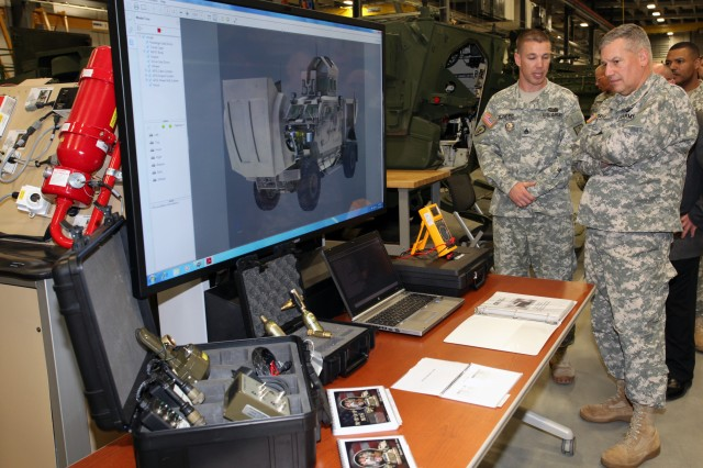 Staff Sgt. Christopher D. Slindee, Wheel Vehicle Mechanic instructor, explains to Lt. Gen. Raymond V. Mason, U.S. Army deputy chief of staff, G-4 (Logistics), the training students receive in troubleshooting and repairing the Mine-Resistant Ambush Protected vehicle Automatic Fire Extinguishing System Dec. 7.