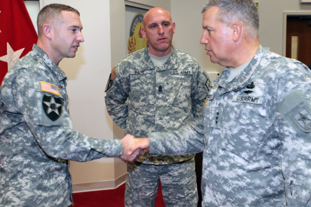 "Lt. Gen. Raymond V. Mason, U.S. Army deputy chief of staff, G-4 (Logistics), presents a coin to Sgt. 1st Class Benjamin O. Hickman, U.S. Army Transportation School, for his ""game changing"" support to the Troops to Trucks credentialing program Dec. 7. The program provides help for Soldiers, with commercial truck driver experience, to obtain a civilian commercial driver's license."