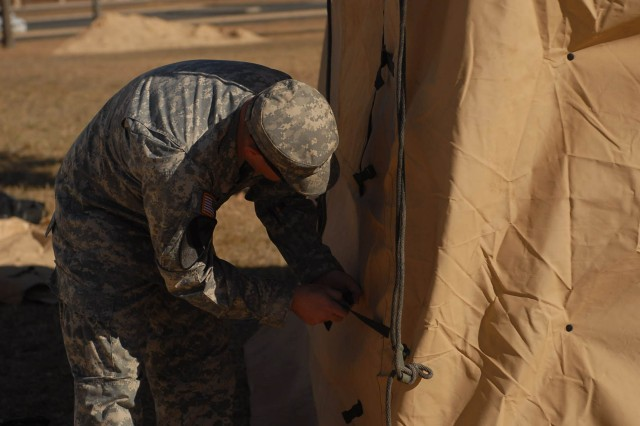 "Sgt. Christopher Judd, assigned to the Headquarters and Headquarters Troop of the 1st Brigade Combat Team ""Ironhorse,"" 1st Cavalry Division, tightens the outer covering of a tent to its supporting pole during a Tactical Operations Center set up at Fort Hood, Texas, Dec. 5, 2012."
