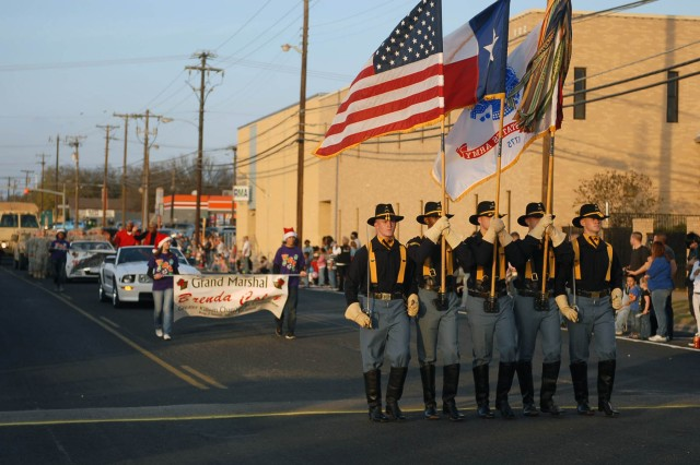 """KILLEEN, Texas--The 1st Cavalry Division's """"First Team"""" Color Guard leads Killeen's 50th Annual Christmas Parade, here, Dec. 8. Maj. Gen. Anthony Ierardi, the First Team's commanding general, served as the parade's grand marshal."""