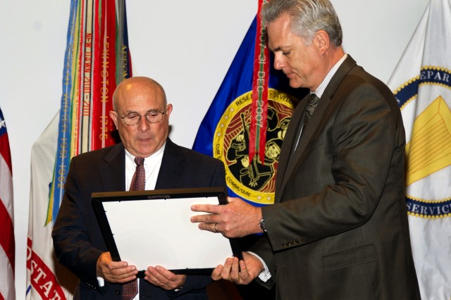 Kevin J. Flamm, executive director, Programs and Technology Transition, Office of the Assistant Secretary of the Army for Acquisition, Logistics and Technology, (right) presents a certificate of appreciation signed by Mary Miller, acting DASA Research and Technology, to Dr. Jay Loomis, Army senior research scientist, upon his retirement from civilian service at the Army Aviation and Missile Research, Development and Engineering Center, Redstone Arsenal, Ala., Nov. 30.