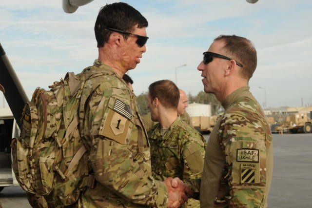 """Retired Army Capt. Samuel Brown shakes hands with Maj. Gen. Robert """"Abe"""" Abrams, 3rd Infantry Division and Regional Command (South) commanding general, upon arrival at Kandahar Airfield, Afghanistan, for Operation Proper Exit, Dec. 6, 2012. Operation Proper Exit brings severely wounded service members back to the theater where they sustained their injuries to provide a firsthand progress update on the continuing mission and to help in the healing process. Brown is from Dallas, Texas. (U.S. Army photo by Sgt. Ashley Curtis)"""