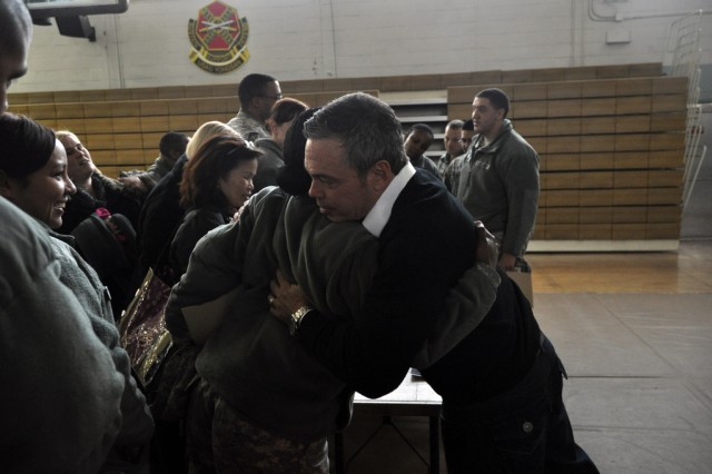 Bernie McGrenahan, a stand-up comedian, hugs and encourages a Soldier after his show at the U.S. Army Garrison Yongsan Collier Community Fitness Center, Dec. 10. (U.S. Army photo by Cpl. Lee Hyokang)