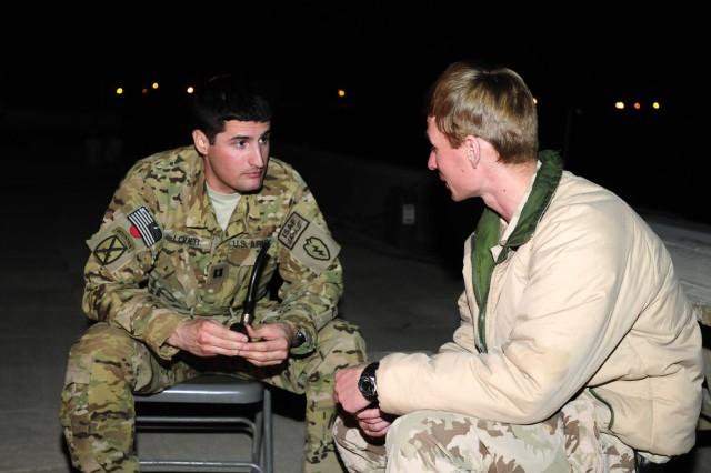Capt. Mike Louer, 25th Combat Aviation Brigade, has a friendly discussion with a liason officer during a casual LNO meeting on the 25th CAB headquarters building on Kandahar Airfield, Afghanistan, Dec. 1.