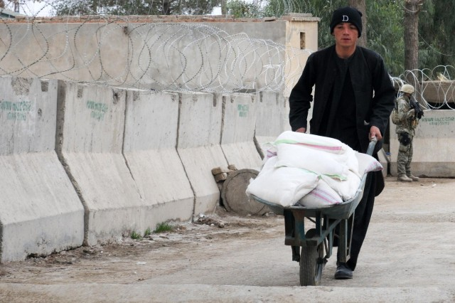 A plain-clothed Afghan Uniformed Police member carries humanitarian assistance to distribute to villagers attending a women's meeting at the Spin Boldak District Center, Kandahar province, Afghanistan, Dec. 7, 2012. The meeting, led by female Afghan leaders from the Government of the Islamic Republic of Afghanistan, non-government organizations and other local professional women, was held in conjunction with the international 16 Days of Activism Against Gender Violence Campaign which runs from Nov. 25 to Dec. 10. Women discussed topics such as women's rights, education, access to medical care and hygiene.