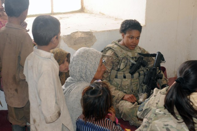 Pfc. Samone Molock, a soldier with the 502nd Military Intelligence Battalion, listens to Afghan women and children during a women's meeting at the Spin Boldak District Center, Kandahar province, Afghanistan, Dec. 7, 2012. The meeting, led by female Afghan leaders from the Government of the Islamic Republic of Afghanistan, non-government organizations and other local professional women, was held in conjunction with the international 16 Days of Activism Against Gender Violence Campaign which runs from Nov. 25 to Dec. 10. Women discussed topics such as women's rights, education, access to medical care and hygiene.