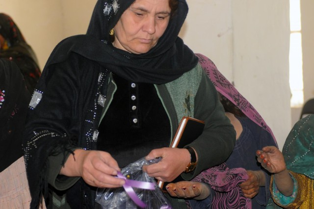 Mahmoona Tarek, a representative from the Women's Economic Empowerment Office distributes purple ribbons which signify participation in the 16 Days of Activism Against Gender Violence Campaign during a women's meeting at the Spin Boldak District Center, Kandahar province, Afghanistan, Dec. 7, 2012. The meeting, led by female Afghan leaders from the Government of the Islamic Republic of Afghanistan, non-government organizations and other local professional women, was held in conjunction with the campaign which runs from Nov. 25 to Dec. 10. Women discussed topics such as women's rights, education, access to medical care and hygiene.