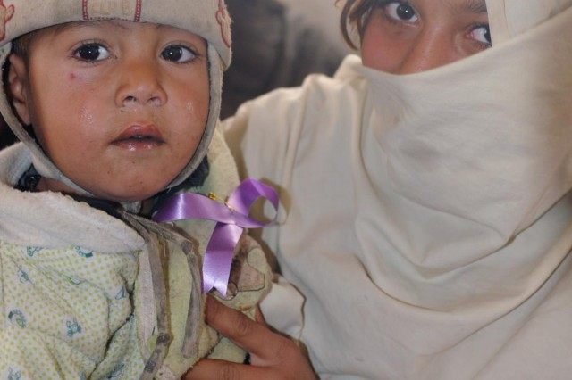 An Afghan woman holds a child wearing a purple ribbon during a women's meeting at the Spin Boldak District Center, Kandahar province, Afghanistan, Dec. 7, 2012. The purple ribbon signifies participation in the 16 Days of Activism Against Gender Violence Campaign which runs from Nov. 25 to Dec. 10. The meeting, led by female Afghan leaders from the Government of the Islamic Republic of Afghanistan, non-government organizations and other local professional women, was held in conjunction with the campaign. Women discussed topics such as women's rights, education, access to medical care and hygiene.