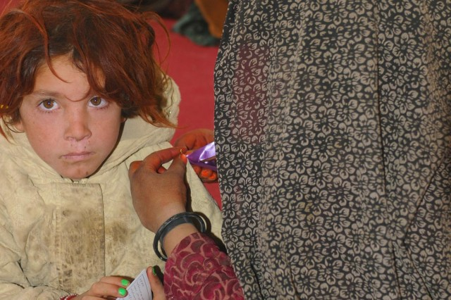 An Afghan woman pins a purple ribbon on a child during a women's meeting at the Spin Boldak District Center, Kandahar province, Afghanistan, Dec. 7, 2012. The purple ribbon signifies participation in the 16 Days of Activism Against Gender Violence Campaign which runs from Nov. 25 to Dec. 10. The meeting, led by female Afghan leaders from the Government of the Islamic Republic of Afghanistan, non-government organizations and other local professional women, was held in conjunction with the campaign. Women discussed topics such as women's rights, education, access to medical care and hygiene.