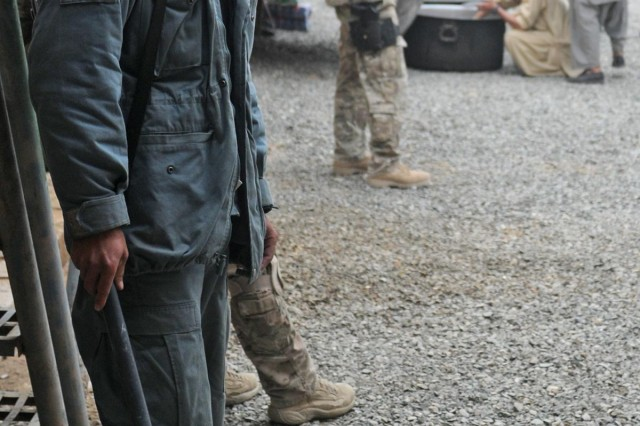 An Afghan Uniformed Police member and coalition forces provide security during a women's meeting at the Spin Boldak District Center, Kandahar province, Afghanistan, Dec. 7, 2012. The meeting, led by female Afghan leaders from the Government of the Islamic Republic of Afghanistan, non-government organizations and other local professional women, was held in conjunction with the international 16 Days of Activism Against Gender Violence Campaign which runs from Nov. 25 to Dec. 10. Women discussed topics such as women's rights, education, access to medical care and hygiene.