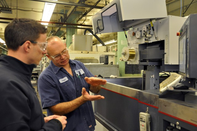 "Benét Lab's Stan Rysio, who is a technician, explaining his cutting process to Shaker High School teacher Brian Ashline. "" at U.S. Army Watervliet Arsenal."
