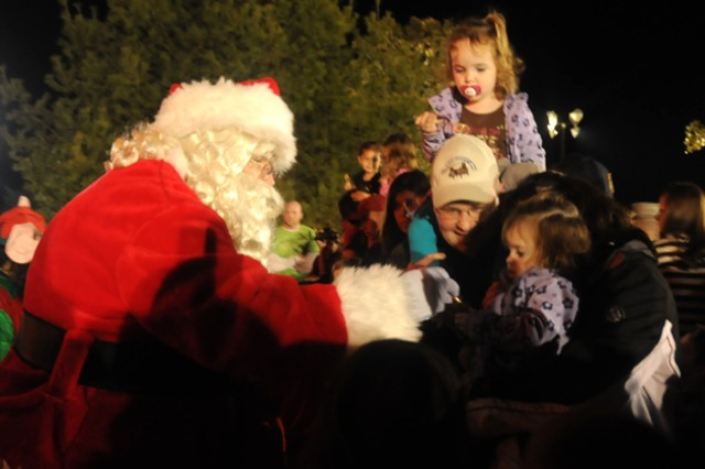 Santa Claus gives out candy to children and listens to their Christmas wishes at the Christmas Tree Lighting Ceremony at Howze Field Dec. 6.