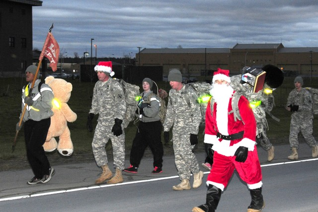 First Sgt. Anthony Hunsaker, senior enlisted adviser of Headquarters and Headquarters Company, 7th Engineer Battalion, 10th Sustainment Brigade, 10th Mountain Division (LI), dressed as Santa to lead Soldiers on a road march carrying toys to be dropped at the USO Fort Drum on Dec. 5. This effort is to support the Mountain of Toys program, which helps ensure that some children of military Families receive some additional assistance this holiday season.