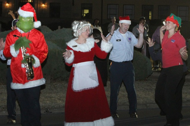 Mrs. Claus and Picerne Military Housing's Jingle Bell Rockers do a festive dance at the Fort Sill holiday tree lighting celebration Dec. 6 in front of McNair Hall. A crowd of about 250 people sang Christmas favorites, and their children met with Santa Claus.