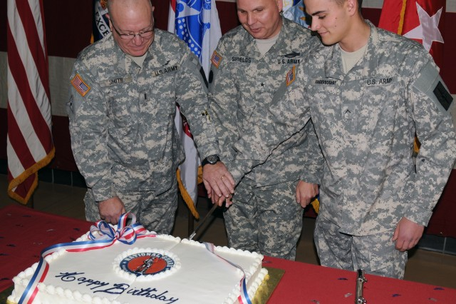 The New York Army National Guard's newest brigadier general, Brig. Gen. Raymond Shields (center) joins Chief Warrant Officer 5 Brian Smith, who enlisted in 1973, and Pvt. Shelbi Vanderbogart, who enlisted Dec. 13, 2011, in cutting the National Guard's Birthday Cake during a ceremony held at New York National Guard headquarters in Latham, N.Y., Dec. 13, 2012, which marked the 376th anniversary of the birth of the National Guard. The celebration has become an annual event.