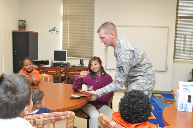 Sgt. Matthew Brewer, 402nd Field Artillery Brigade, offers pieces of the Hooah bar from a Meal Ready to Eat to the brigade's Partners in Education students at Dr. Sue Shook Elementary School in El Paso, Texas, Nov. 30. Students were dubious at first, but those who were brave enough to try the snack bar said they liked it. (Photo by Staff Sgt. Patricia Deal, 402nd Field Artillery Brigade, Division West, Public Affairs)