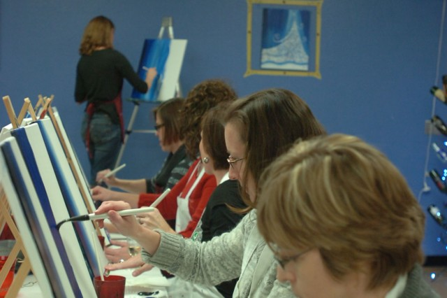 HARKER HEIGHTS, Texas-- Spouses of Soldiers assigned to 1st Cav. Div.'s Headquarters paint their blank canvases blue in efforts to recreate a portrait themed A Twinkling Christmas Tree during a session at Painting with a Twist, here, Dec. 11.