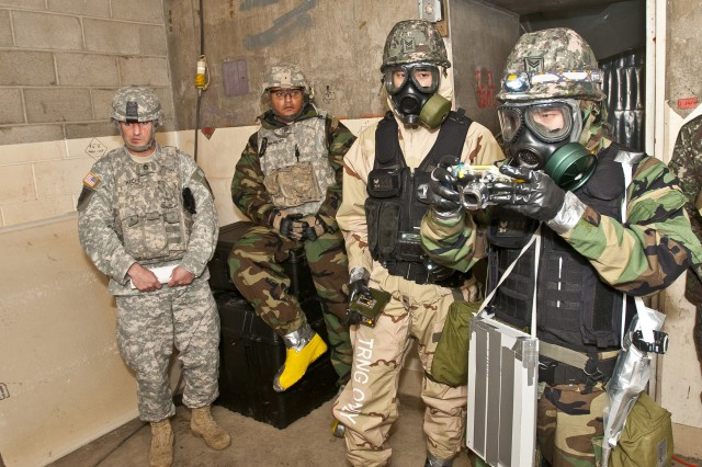 Sgt. 1st Class Jang Won Park, (right), and Sgt. 1st Class Jin Young Noh (middle), both assigned to the 24th Korean Chemical Special Forces Battalion, from South Korea, photograph a chemical lab setup Dec. 13 during a weeklong training exercise in Elma, Wash., with the 11th Chemical Company, 110th Chem. Battalion (Technical Escort), out of Joint Base Lewis-McChord, Wash. The mission, which had a Korean team removing a simulated mustard gas agent from an abandoned facility, culminated the week.