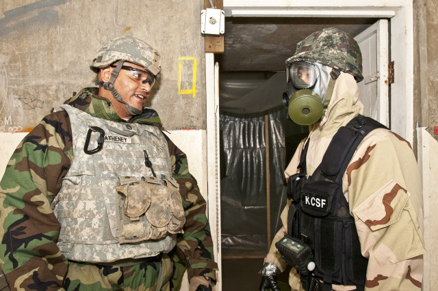 Sgt. 1st Class Jason Matheney, a team leader with the 11th Chemical Company, 110th Chem. Battalion (Technical Escort), out of Joint Base Lewis-McChord, Wash., compliments Sgt. 1st Class Jin Young Noh, assigned to the 24th Korean Chemical Special Forces Battalion, from South Korea, on a job well done Dec. 13 during a weeklong training exercise with Matheney's company in Elma, Wash. The mission, which had a Korean team removing a simulated mustard gas agent from an abandoned facility, culminated the week.
