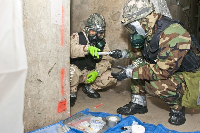Korean soldiers assigned to the 24th Korean Chemical Special Forces Battalion, from South Korea, process chemical samples Dec. 13 during a weeklong training exercise in Elma, Wash., with the11th Chemical Company, 110th Chem. Battalion (Technical Escort), out of Joint Base Lewis-McChord, Wash. The mission, which had a Korean team removing a simulated mustard gas agent from an abandoned facility, culminated the week.